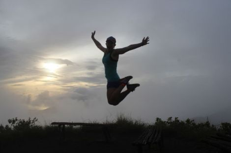 Mel jumps for joy after climbing her first volcano in Bali.
